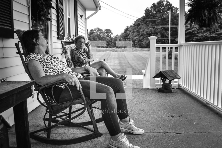 mother and adult daughter sitting in rocking chairs on a front porch