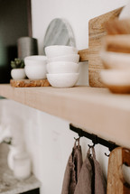 marble cutting board and bowls on a wood shelf