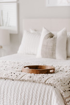 wooden tray on a made bed