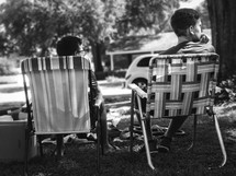 brothers sitting outdoors in lawn chairs