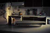 an iron and ironing board on a kitchen counter