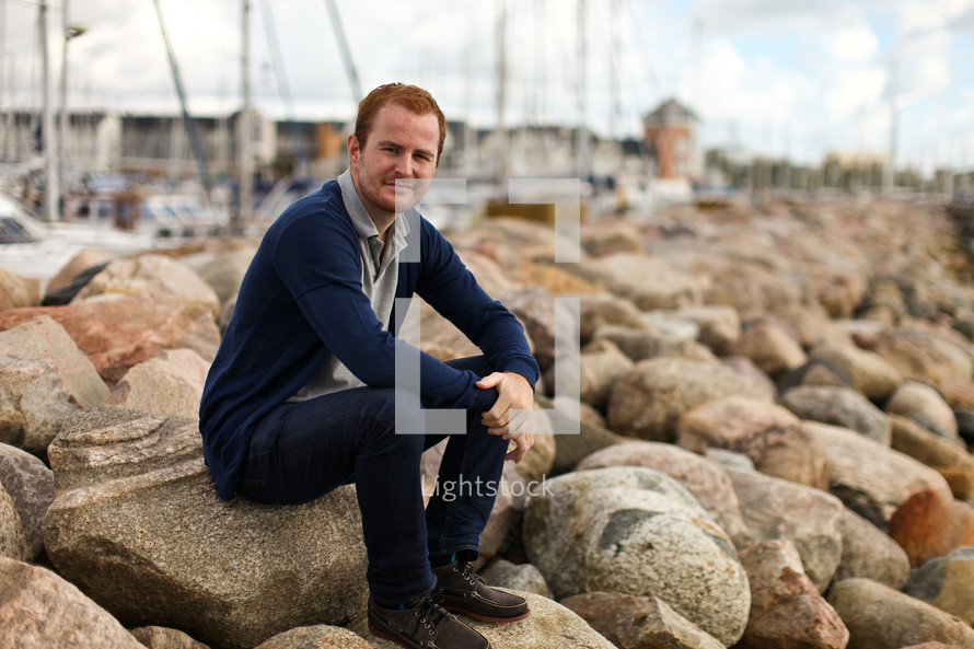 Man sitting on a rocky shore
