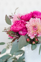 A bouquet of pink peonies in a white vase.