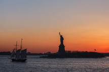 statue of liberty and ship at sunset