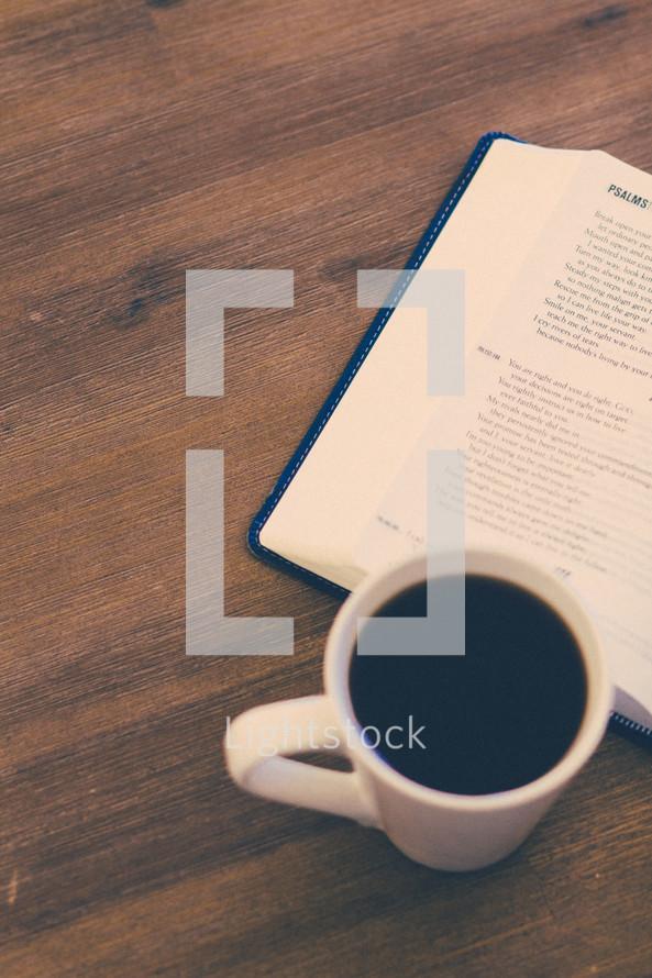open Bible and coffee mug on a wood floor
