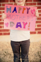 A photo of a kid making a Mother's Day Card