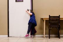 a child peeking out a door