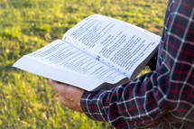 man reading the Bible outdoors