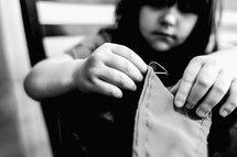 a child sewing with a needle and thread