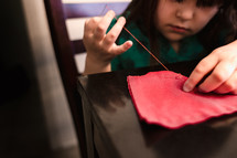 a child sewing with needle and thread