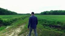 a man walking on a path through a field outdoors