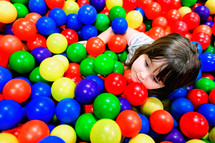 girl child playing in a ball pit