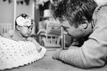A father watching his newborn daughter with loving eyes