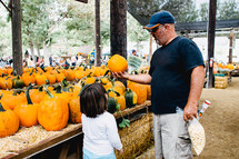 father and daughter picking out a pumpkin