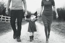 a mother and father walking holding hands with their daughter daughter down a gravel road