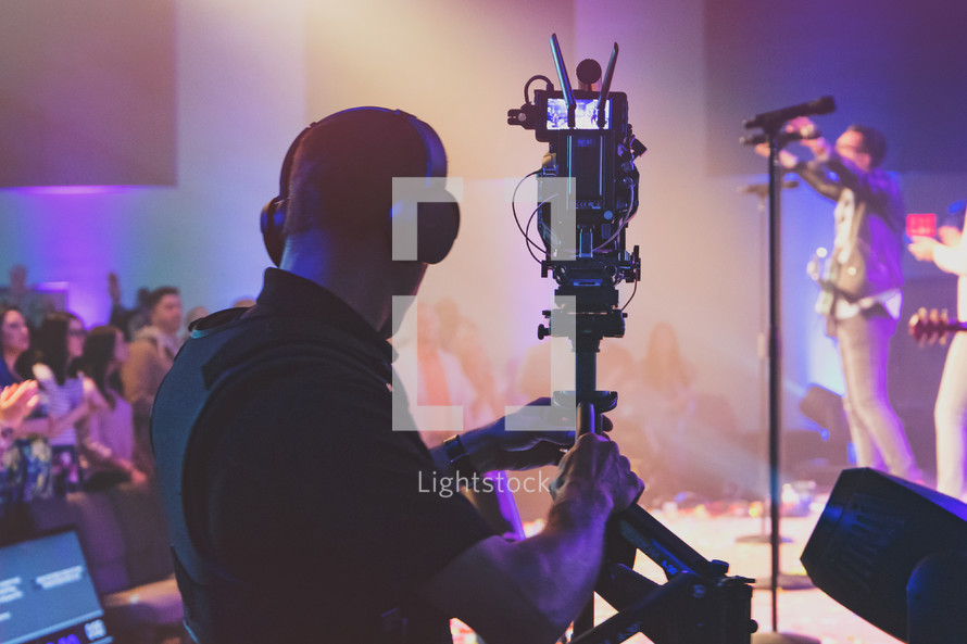 Media team member with camera live streaming a church concert