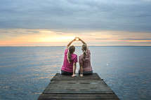 sisters sitting at the end of a dock making a heart with their hands