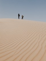 men standing at the top of a sand dune