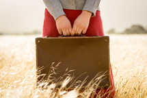Girl holding suitcase in Brown Grass