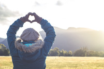 a woman standing outdoors in winter making a heart with her hands