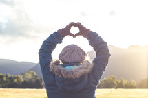 a woman standing outdoors in winter making a heart shape with her hands