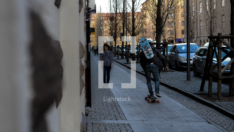 man skateboarding on a sidewalk in Gothenburg, Sweden