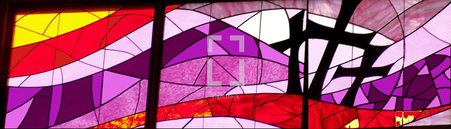 A beautiful stained glass window adorned with ribbons of lavender, purple, red and yellow depicting the three crosses of the crucifixion of Jesus and the two thieves on Mount Calvary otherwise known as Golgotha the place of the skull.