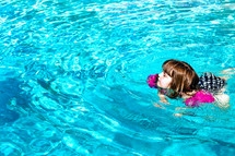a girl child swimming in a pool