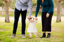 mother and father holding hands with their infant daughter