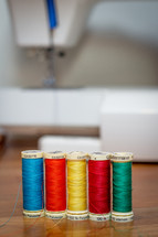 Row of Thread with Sewing Maching Background