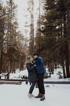 a couple kissing outdoors in snow