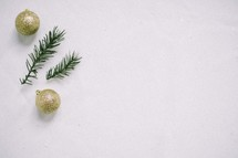 gold glitter ornaments and pine needles in snow
