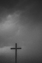 Silhouette of a wooden cross under a stormy sky.
