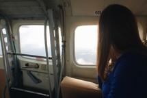 woman looking out a plane window