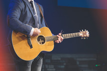 Worship leader in suit with an acoustic guitar at Easter