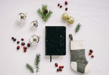 Bible in the snow with a spruce twig, red berries, sock, gold ornaments