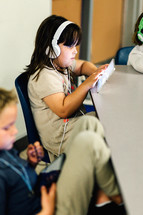 a child with headphones using a tablet in a classroom