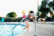 a child stepping out of a pool