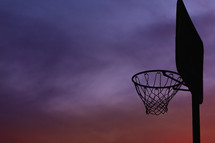 silhouette of a basketball goal at sunset