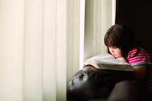 a girl reading a Bible on the arm of a couch