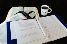 a list in a three ring notebook and an open Bible