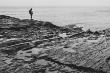 a woman with a backpack standing on a rocky shore