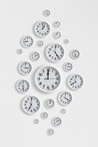 Many round clocks on a white wall.