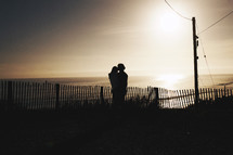 Couple embracing on beach at sunset.