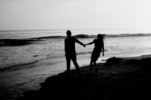 couple walking together holding hands on a beach
