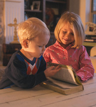 brother and sister reading a Bible together