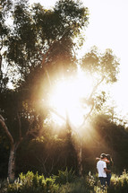 sunburst through the trees over a couple hugging