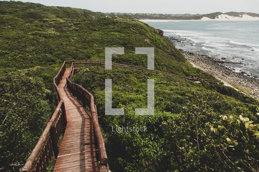wooden boardwalk path leading to a shore