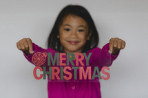 girl holding a Merry Christmas sign