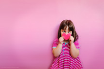 a child in a dress holding a paper heart